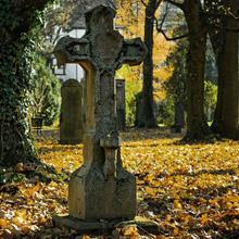 Kreuz auf Friedhof im Herbst